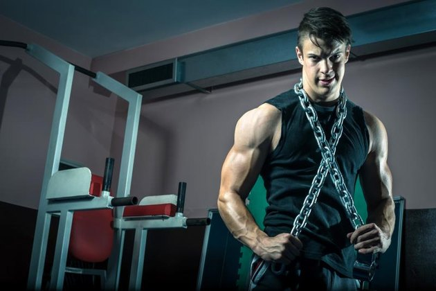 Young adult man posing in gym wearing iron chain around neck.