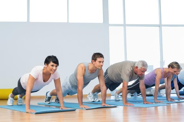 A group of young and old men and women perform push-ups on yoga mats at a sunny gym.