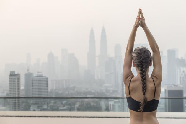 Woman doing yoga on the roof of a skyscraper in a big city.