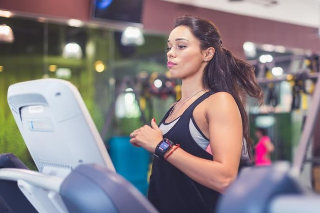 Fit women doing cardio exercises, running on treadmills in the gym