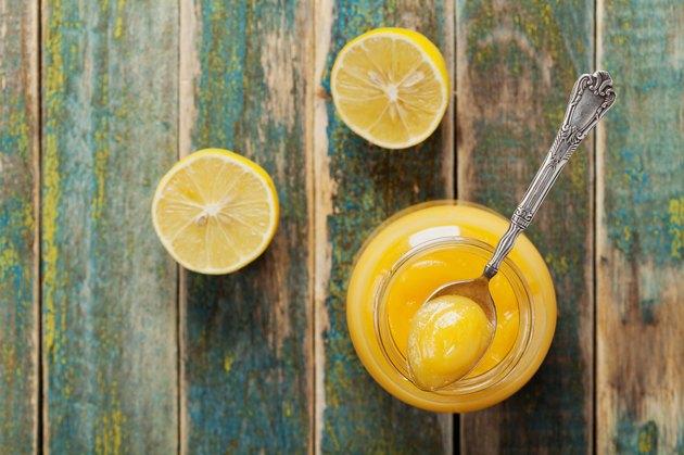 Lemon curd in jar on rustic wooden table, top view