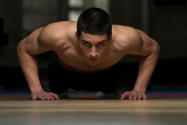 Young Athlete Doing Push-Ups As Part Of gym Training