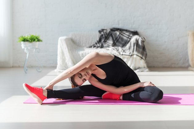 Fit woman high body flexibility stretching her leg and back