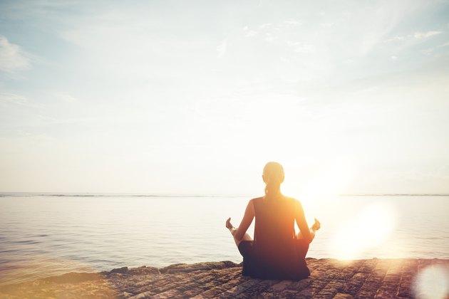 Woman doing meditation practice on the beach