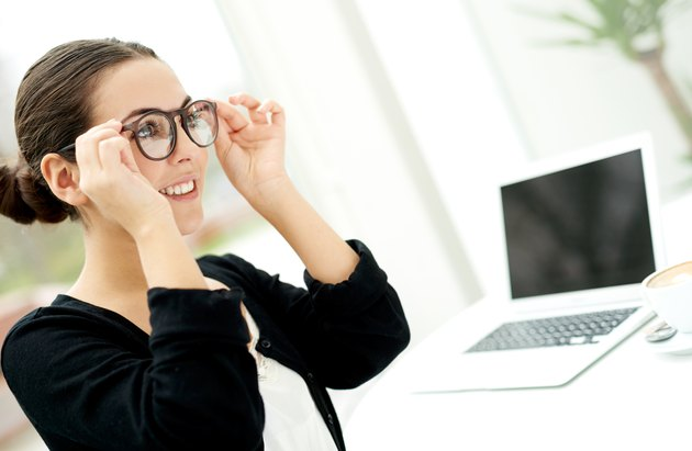 Young businesswoman adjusting her glasses