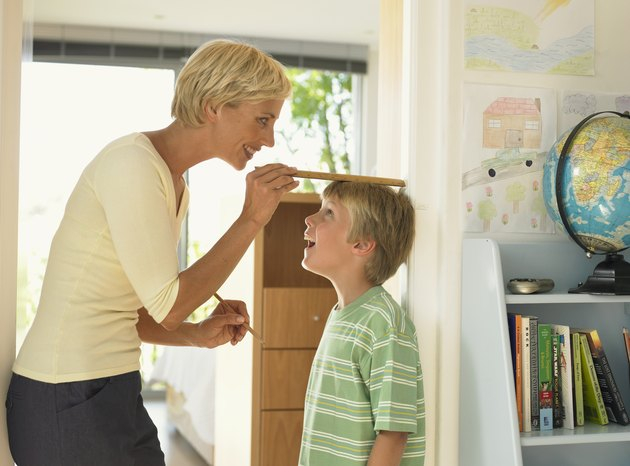 Mother measuring son's (7-9) height against wall, smiling
