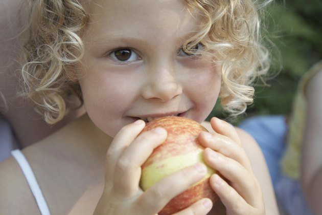 Girl (3-5) holding apple to mouth, smiling, portrait, close-up