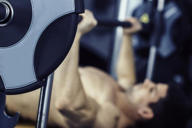 Man lifting weights, lying on bench press in gym. Focus on weight plate, model blurred. Color graded image, convenient copy space.