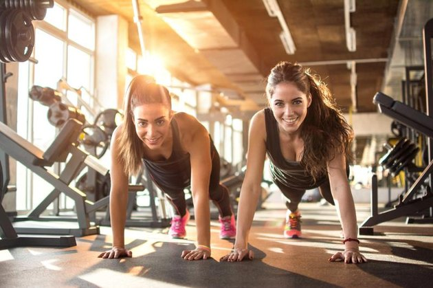 Two sporty girls doing push ups in gym.