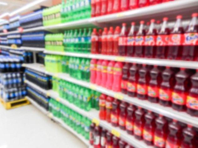 Soda bottles on display on shelves in a supermarket.