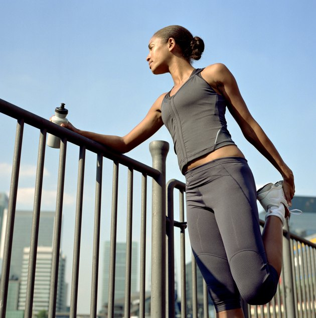 Female runner leaning on railing, stretching leg