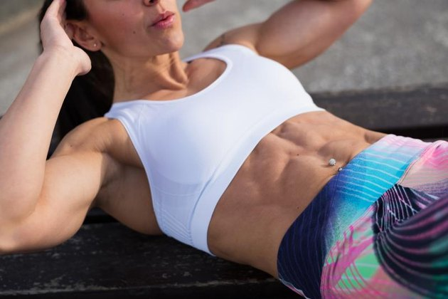 Fit strong stomach abdominal muscles closeup. Fitness woman doing crunches exercise workout. Female fit athlete training midsection for  improve core strength.