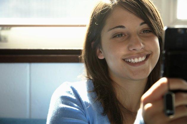 Teenage girl (15-17) using mobile phone, smiling (focus on girl)