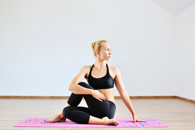 Young woman in half spinal twist pose on mat