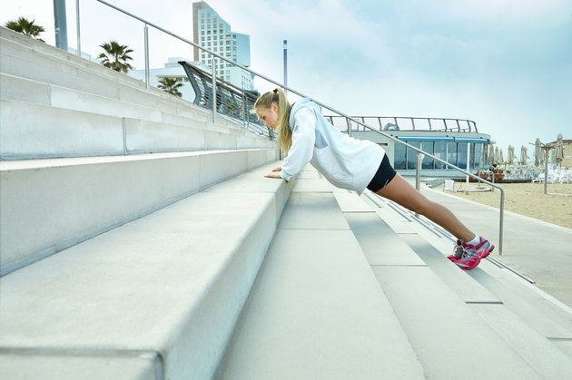 Lady doing pushups by the stairs outdoors by beach