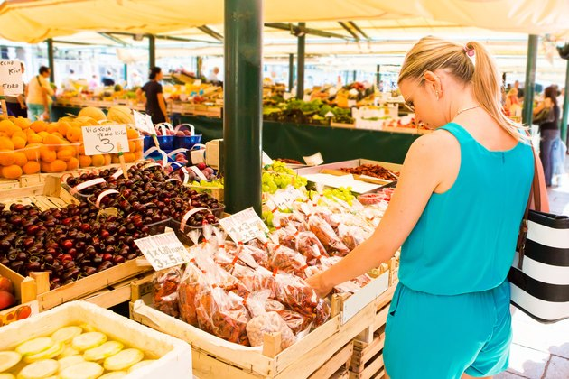 Healthy young woman shopping farmers market fresh fruits and vegetables