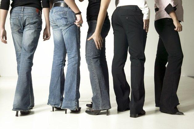 Women wearing denim jeans, posing in studio, low section