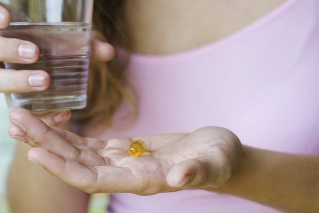 Young woman holding vitamin pill and glass of water, cropped