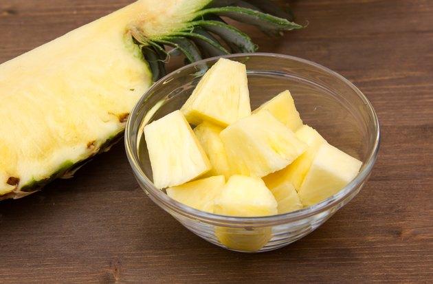 Pineapple cubes on bowl on wood