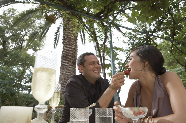 Couple at table, man feeding woman strawberry, low angle view