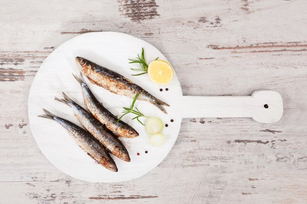 Grilled sardines on wooden plate.