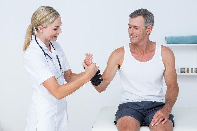 Doctor examining a man wrist