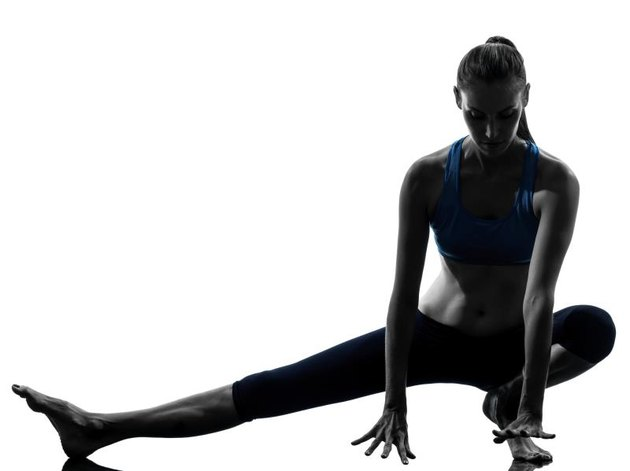 one caucasian woman exercising yoga stretching legs warm up in silhouette studio on white background