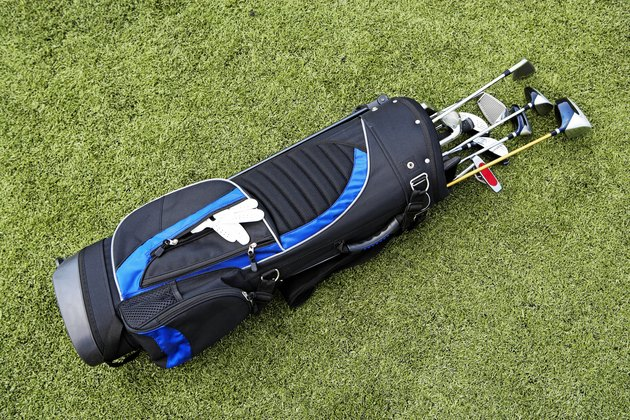 Golf clubs and golf bag on artificial turf, elevated view