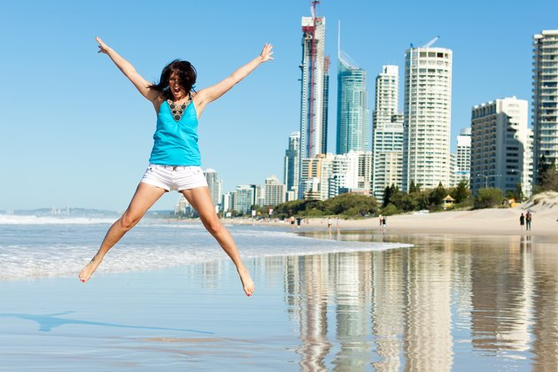 atractive woman jumps with joy on the beach