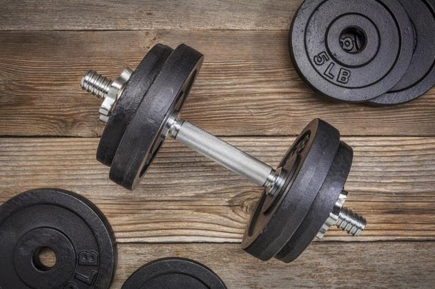 exercise weights - iron dumbbell with extra plates on a rustic wooden deck