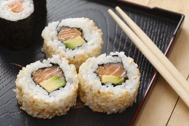sushi rolls  on black plate and chopsticks