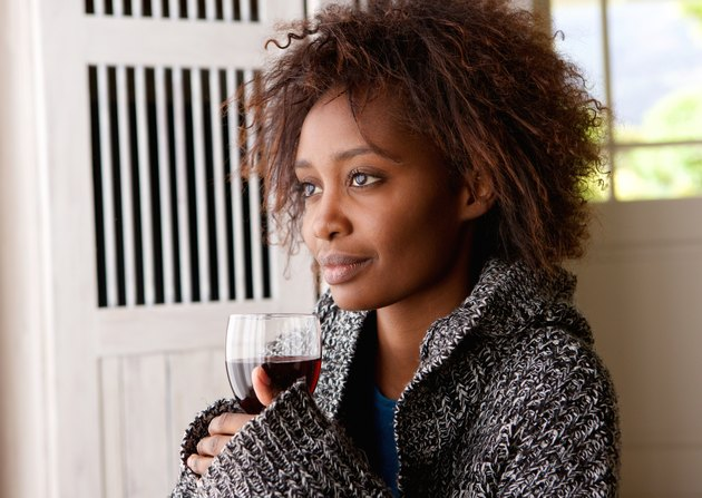 Beautiful african woman holding glass of wine