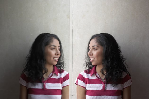 Side profile of a young woman looking at her reflection