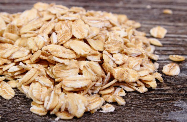 Heap of oat flakes on wooden background