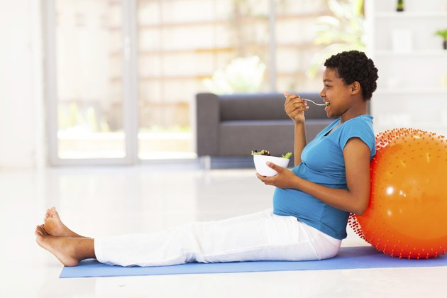 pregnant african american woman eating healthy salad on exercise mat