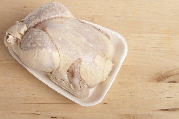 Frozen chicken on cutting board.
