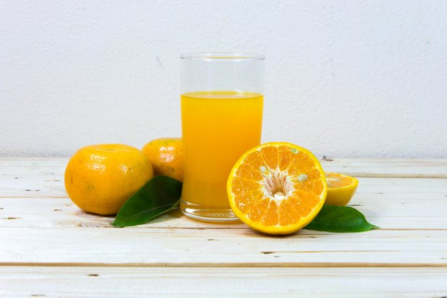 Glass of orange juice and slices of orange on wooden