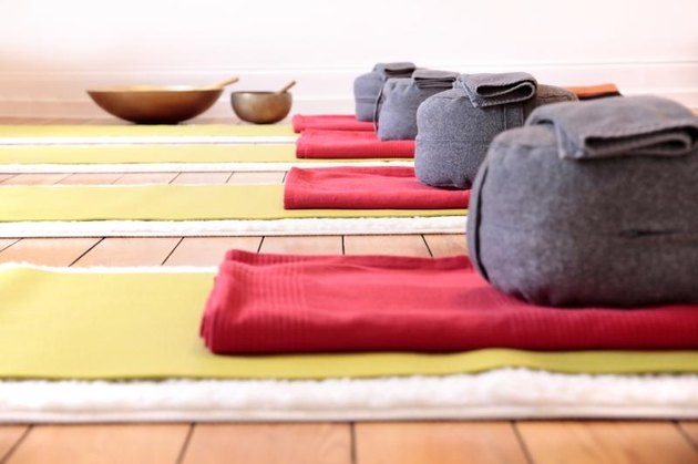 Close-up of yoga mats and yoga cushion in yoga studio