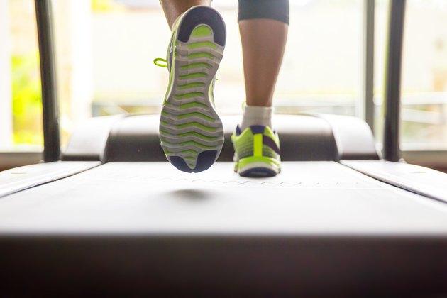 Close up woman feet running on treadmill