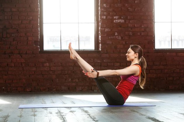 Woman doing yoga in the loft space with brown brick wall
