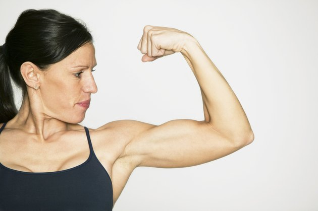 Young woman flexing muscles in studio, portrait