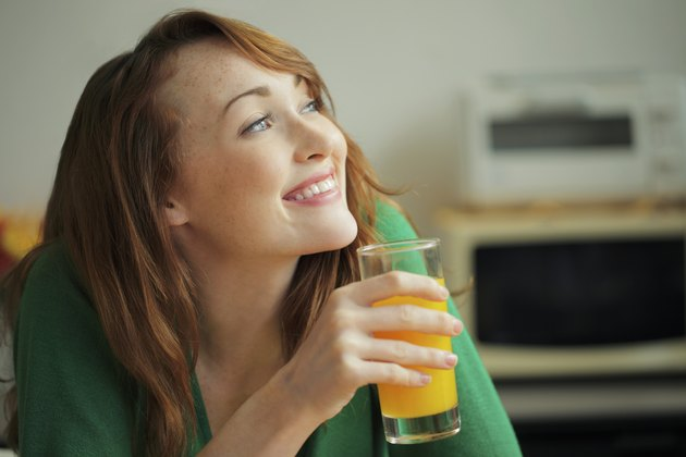 Young woman holding glass of orange juice and smiling