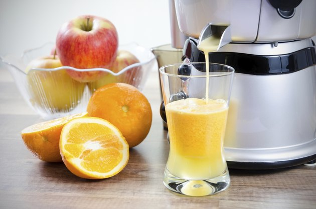 Juicer and orange juice. Fruits in background