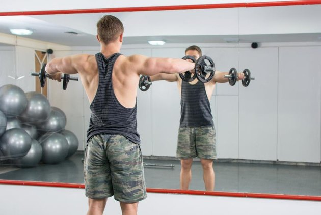 Man performing shoulders workout at the gym