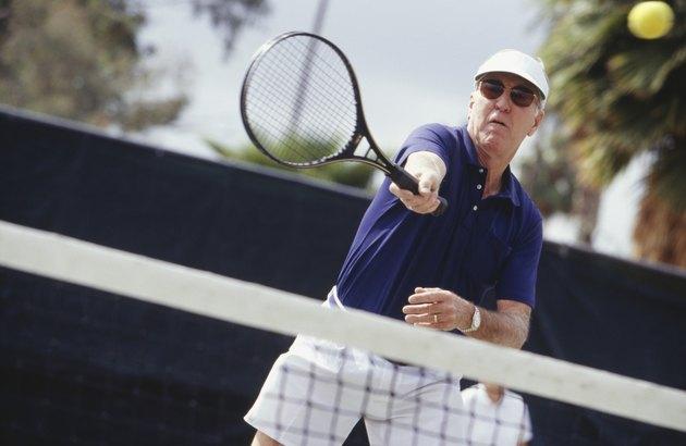 Man wearing sunglasses playing tennis outdoors