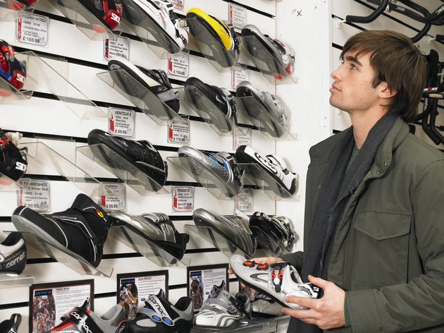 Young man looking at trainers in shoe shop, side view