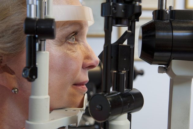 Woman getting eye exam with a slit lamp