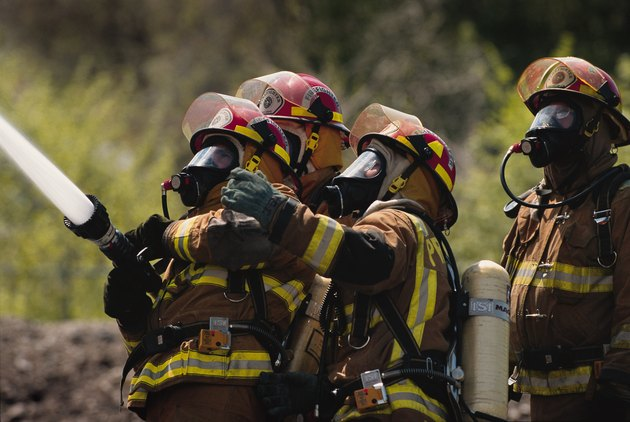 a group of firefighters in full gear dowse a fire with a firehose