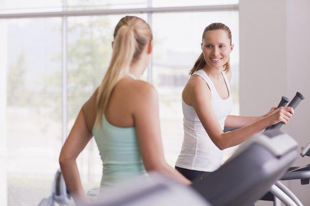Smiling women using exercise equipment in gymnasium