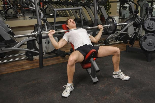 Young man surrounded by weights does a barbell incline bench press exercise at the gym.